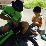 自転車の修理を手伝う男の子